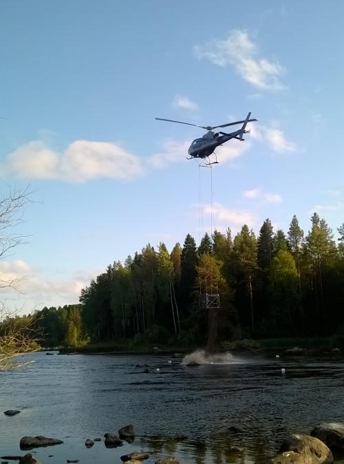 Helikopteri pudottaa soraa koskeen.