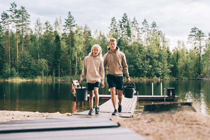 Mies ja poika kävelevät kohti kameraa ämpärit kädessä. Taustalla näkyy vesistö ja laituri.