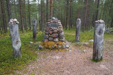 Kivistä kasattu muistomerkki, jota ympäröi neljä pystyssä olevaa puupölkkyä.