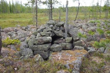 Kookkaista kivistä kasattu keko rakan reunalla.
