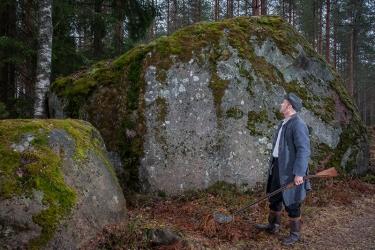 Harmaaseen pitkään takkiin pukeutunut mies katsoo suurta sammaleista kiveä kivääri kädessään.