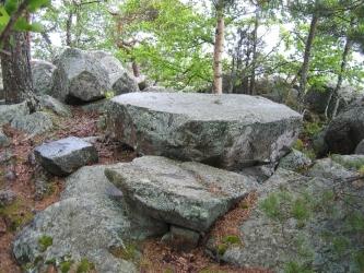 Tasapintainen suuri kivi kivisessä ympäristössä.