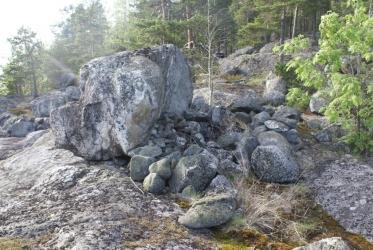 Kallioisessa maastossa oleva suuri rantakivi, jonka toisella puolen on röykkiö pienempiä kiviä.