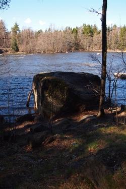 Iso kivi joen rannassa puiden varjossa.