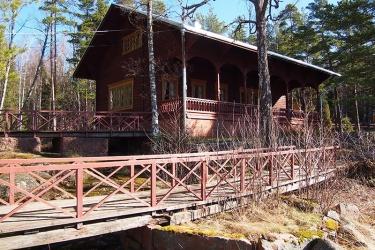 Kaksi puusiltaa sekä mökki, jossa on koristeelliset ikkunat ja koko mökin levyinen kuisti.