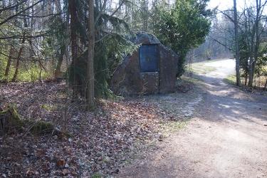 Tien varressa oleva siirtolohkare, jonka seinämällä on suuri muistolaatta.