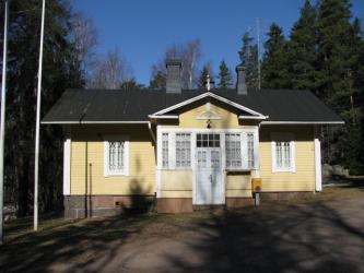 Talo, jossa on veranta, valkoiset ulko-ovet sekä koristeelliset valkokarmiset ikkunat. Talon katolla on kaksi savupiippua ja antenni. Verannan nurkalla on Postin kirjelaatikko.