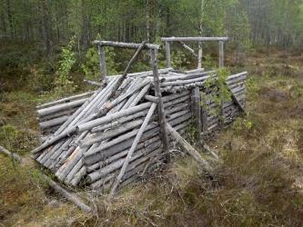 Kuorettomista puuriu'uista tehty rakennelma metsässä.