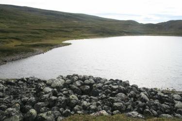 Kiviä lammen rannalla tunturimaisemassa.