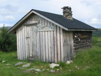 Tunturimaisemassa tupa, jonka katolla on savupiippu ja yhdellä seinustalla poronsarvet.