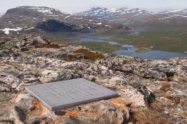 Muistolaatta kalliolla jylhissä tunturimaisemissa.