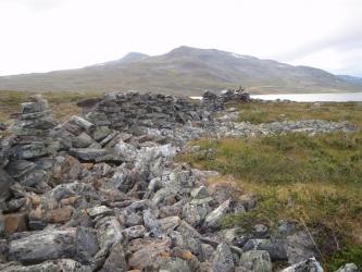 Päällekkäin ladottuja kiviä kaarteena tunturimaisemassa.