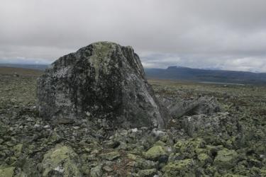 Tunturimaisemassa siirtolohkare, jonka ympärillä on paljon kivikkoa.