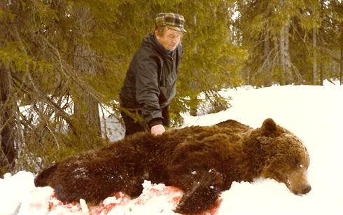Mies seisoo nojaten karhuun, joka makaa kuolleena lumihangessa.