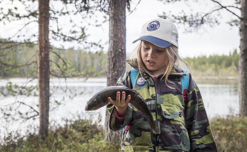 Tyttö seisoo järven rannalla ja katsoo kädessään olevaa kalaa.