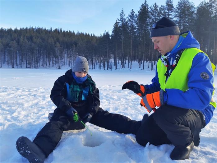 Kalastuksenohjaaja Matti Kulju on kyykistyneenä pilkkivän pojan viereen ja neuvoo häntä kalastamisessa.