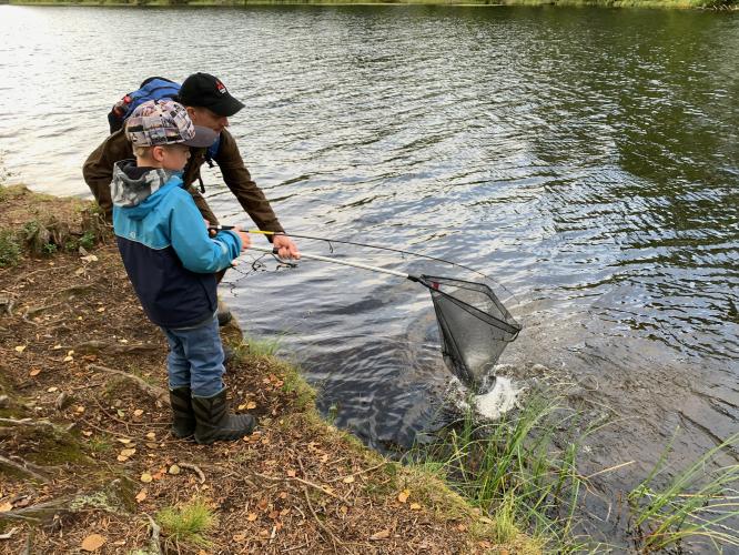 Poika on saanut kalan, jonka mies auttaa nostamaan haavilla.