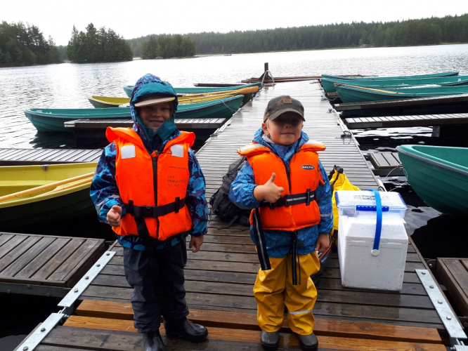Kaksi poikaa seisoo laiturilla pelastusliivit päällä ja näyttää peukkua